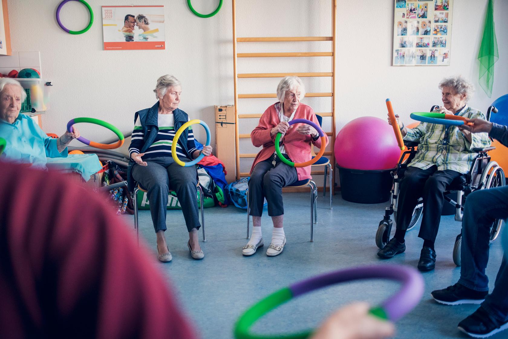 Bewohnerinnen bei morgendliche Gymnastik mit bunten Reifen im Stuhlkreis