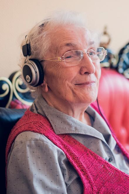 Seniorin hört mit Kopfhörern Märchen im Mutter Eva von Tiele Winckler-Pflegeheim in Wentorf.
