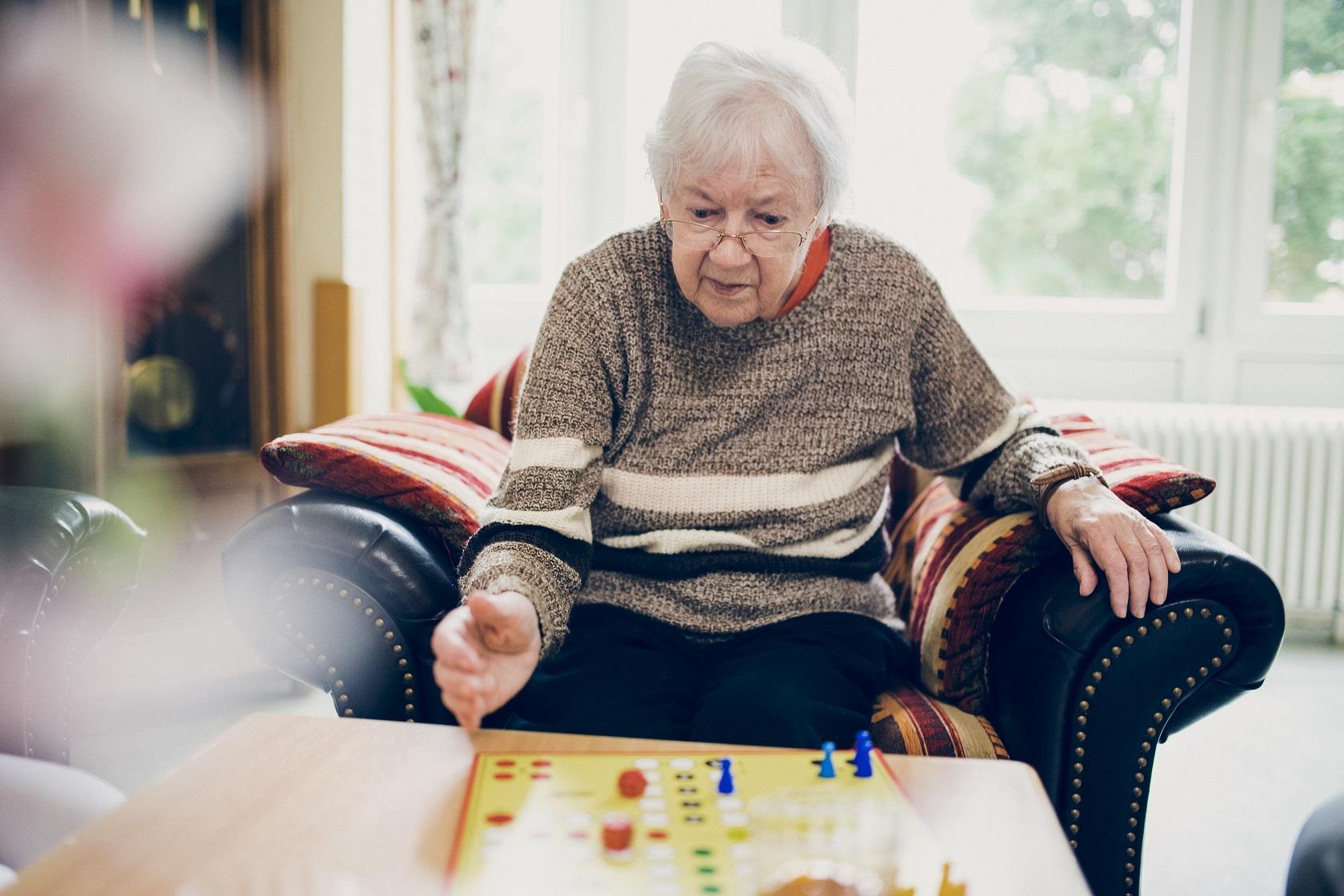 Eine Bewohnerin spielt ein Brettspiel