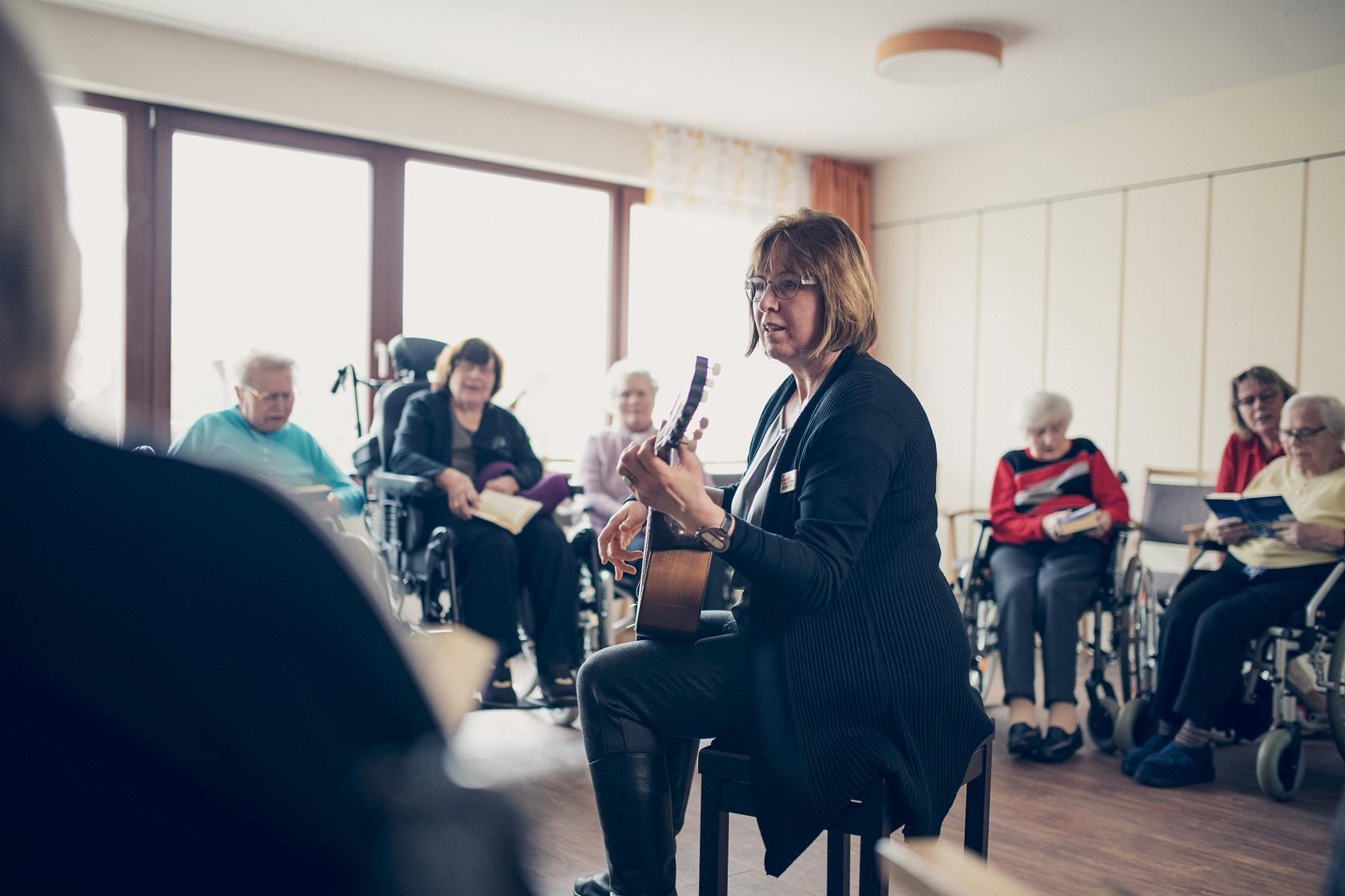 Eine Mitarbeiterin spielt Gitarre und singt mit den Bewohnern