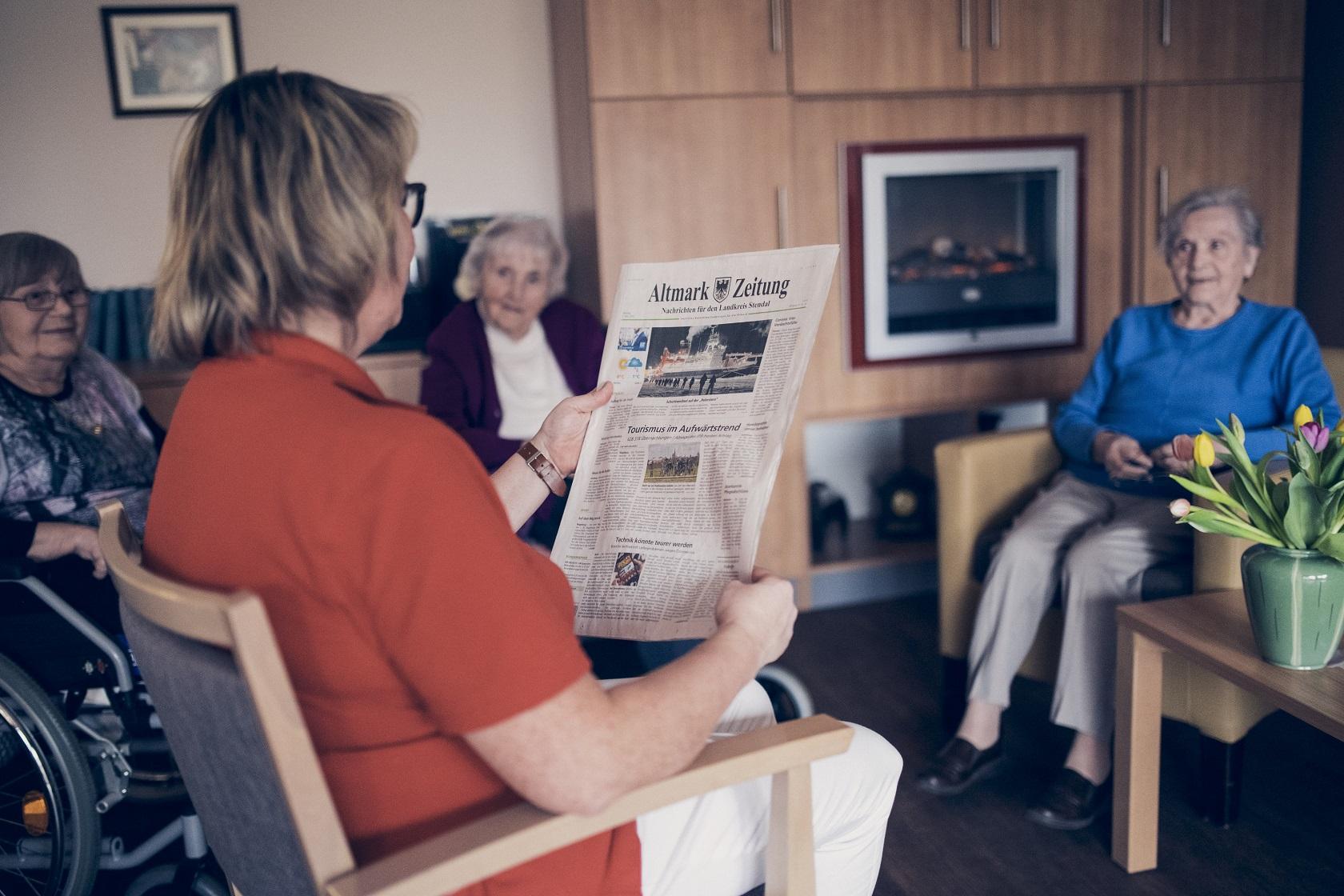 Eine Mitarbeiterin liest täglich eine Zeitung mit den Bewohnern