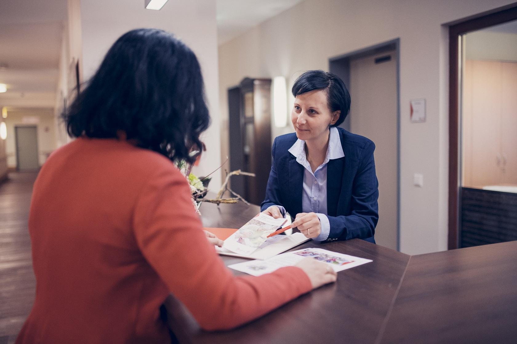 Eine Mitarbeiterin erklärt ein Dokument