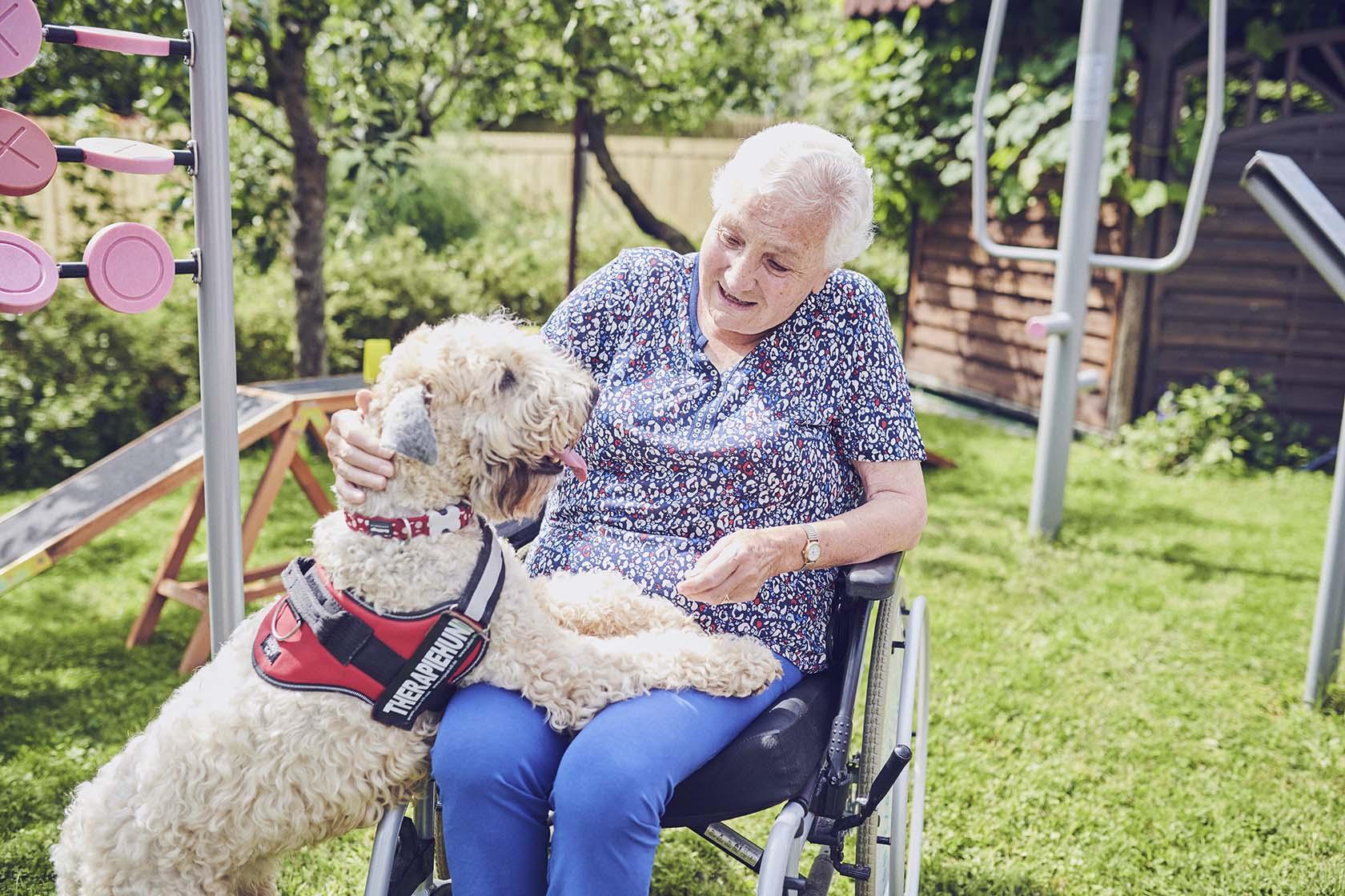 Eine Bewohnerin streichelt einen Therapiehund