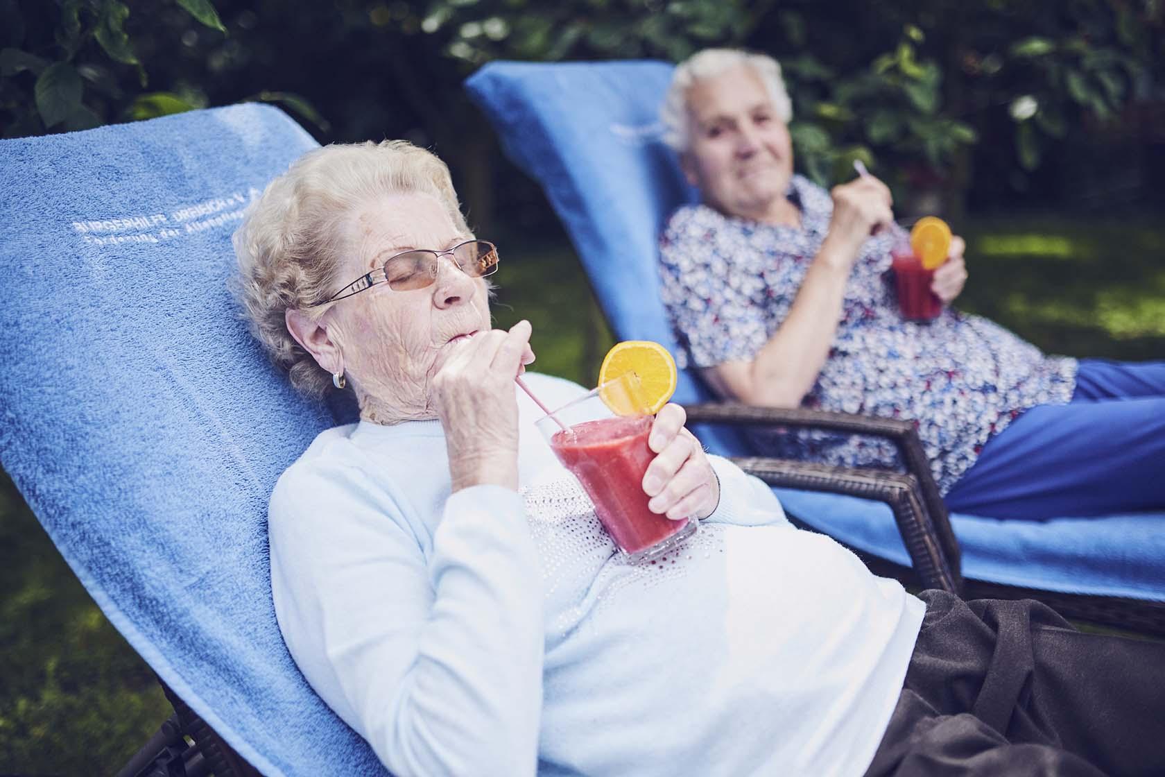 Zwei Bewohnerinnen im Liegestuhl genießen ein Kaltgetränk