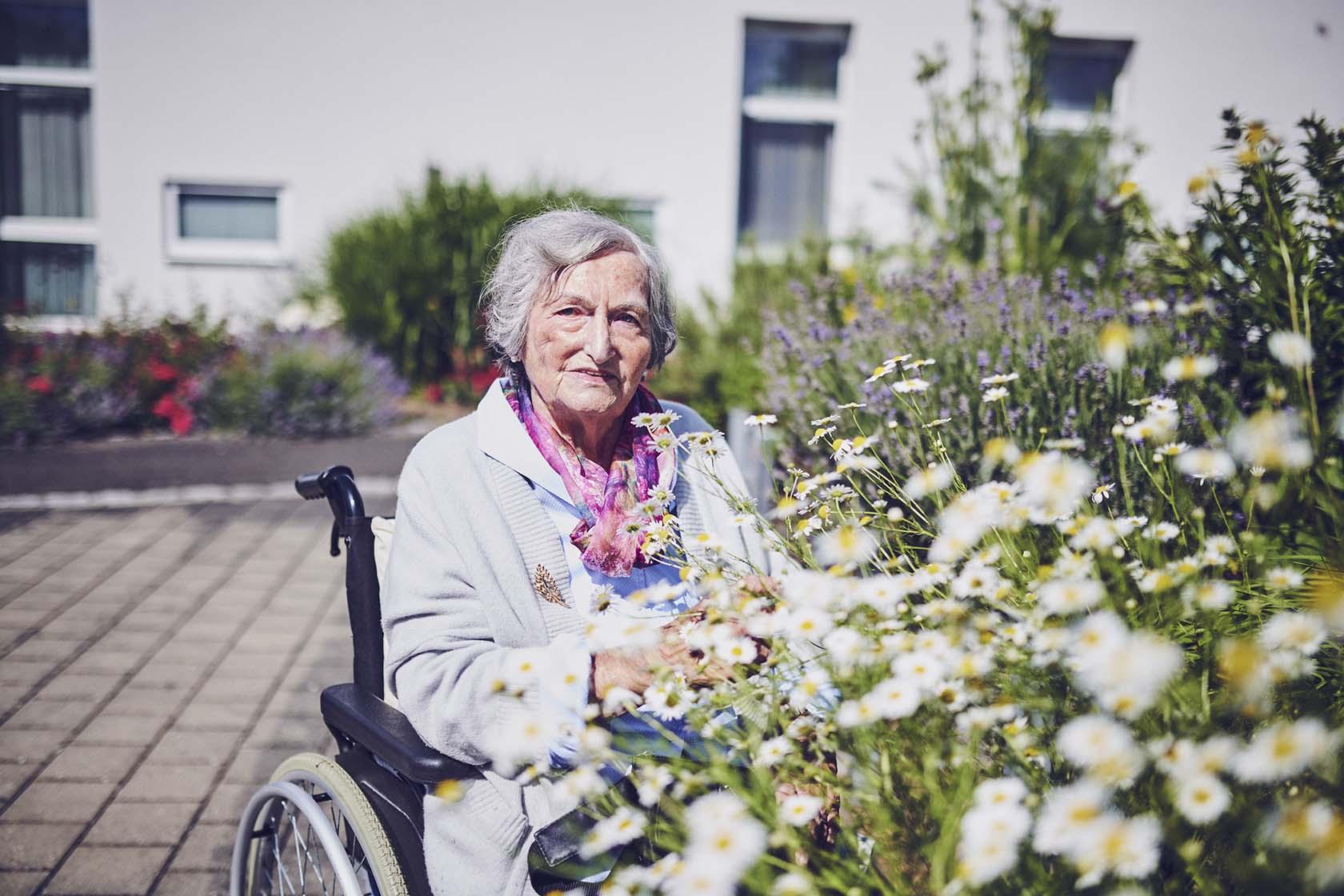 Eine Bewohnerin genießt den Duft der Blumen