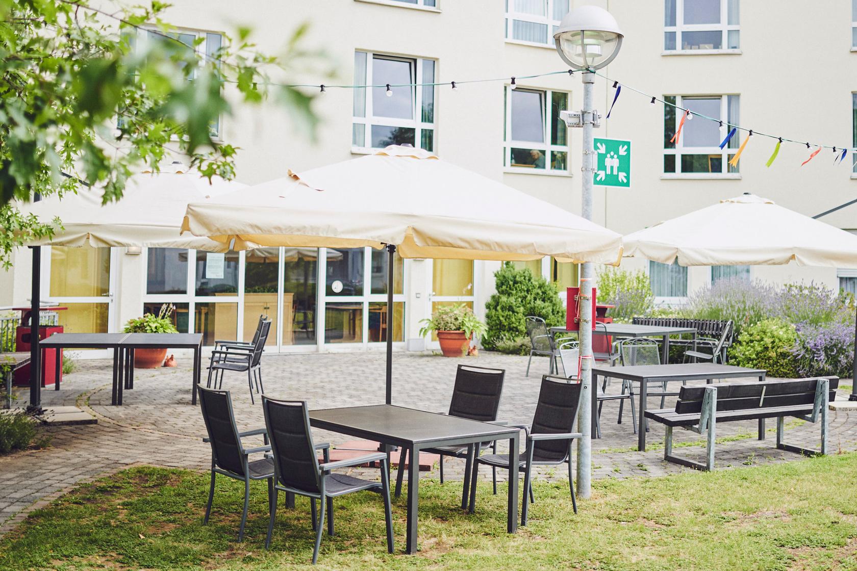 Tisch, Stühle und Sonnenschirme im Innenhof, Johanniter-Stift Duisburg