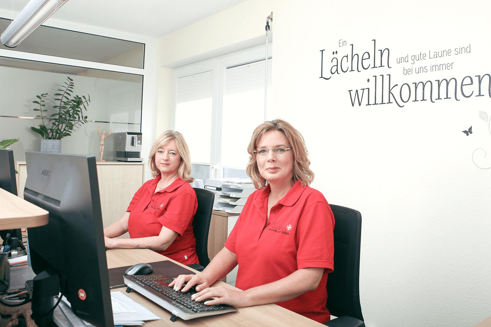 zwei Frauen in roten Poloshirts hinter einer Empfangstheke