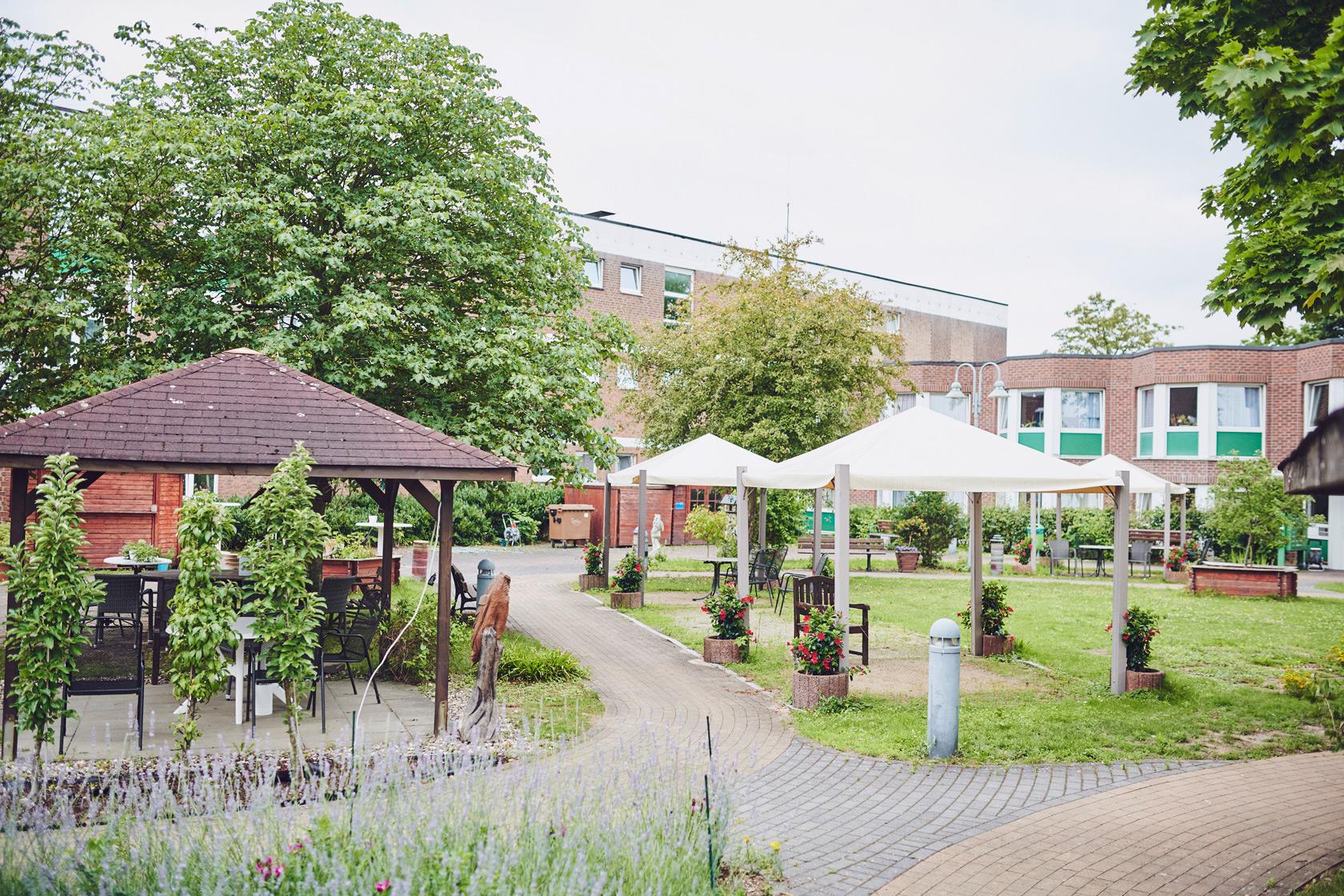 Garten mit Gartenmöbel im Johanniter-Stift Heuserhof in Köln.