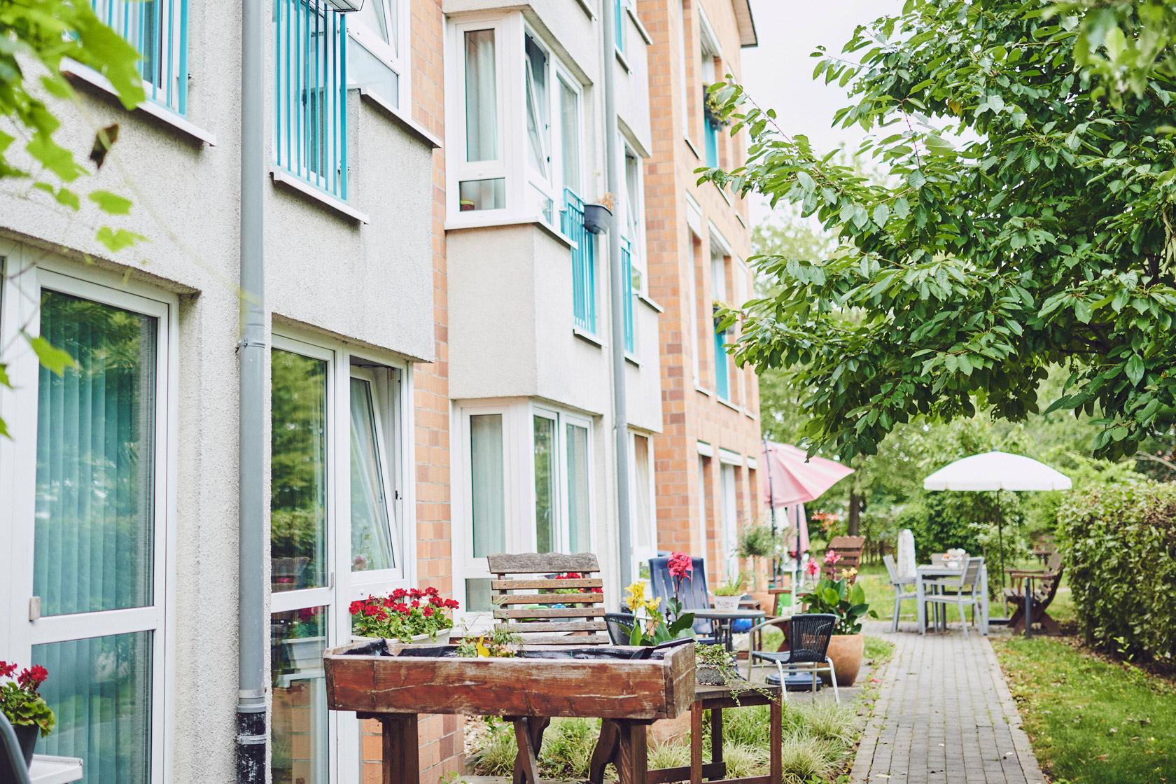 Außenansicht mit Sitzgelegenheiten und Hochbeeten am Johanniter-Stift Meerbusch