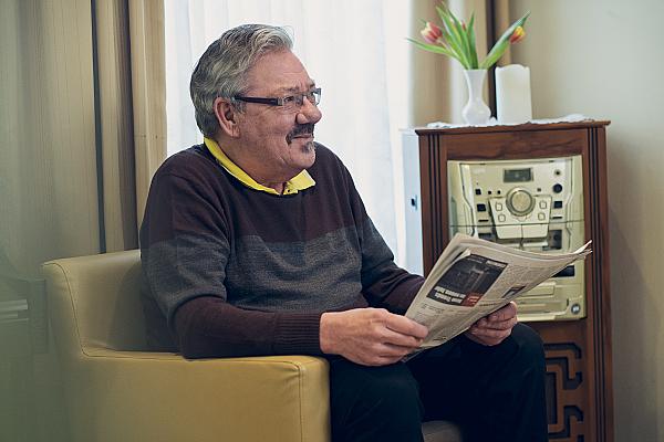 Ein älterer Herr wirf einen Blick in die Tageszeitung