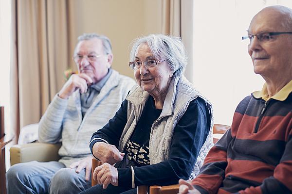 Drei Bewohnende lauschen einer Person im Gruppenangebot
