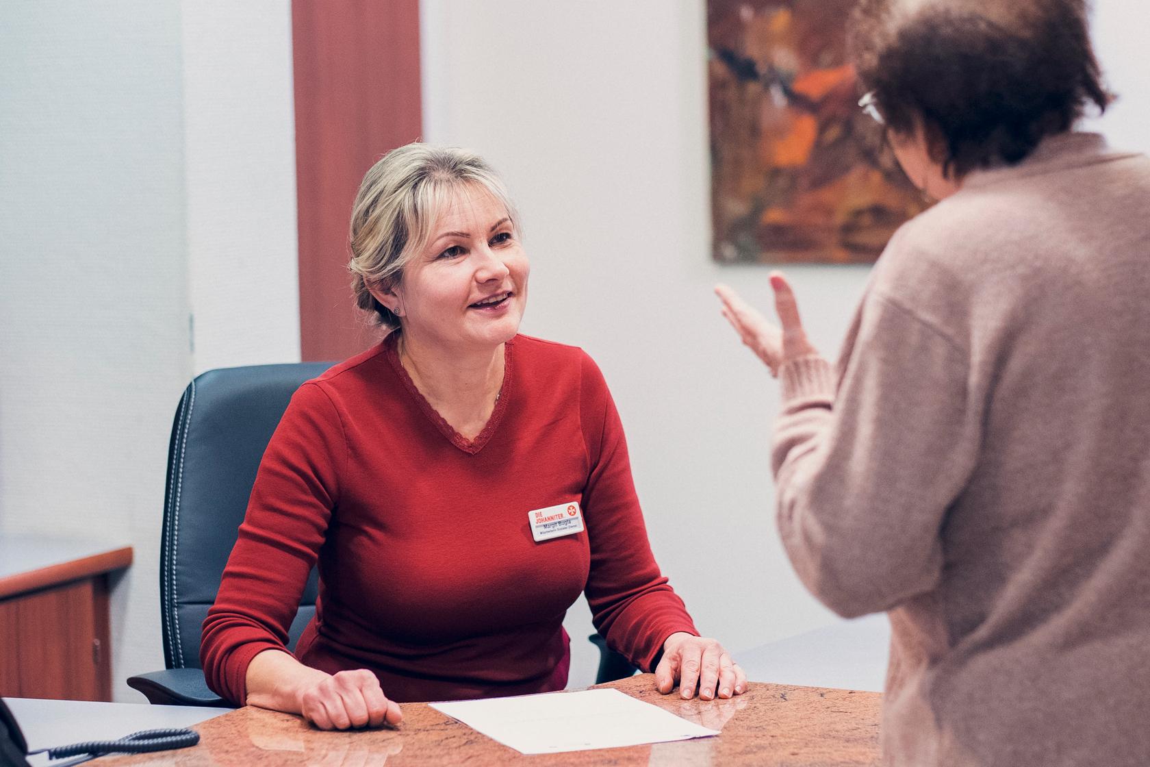 Frau im roten Pullover am Schreibtisch berät eine Bewohnerin
