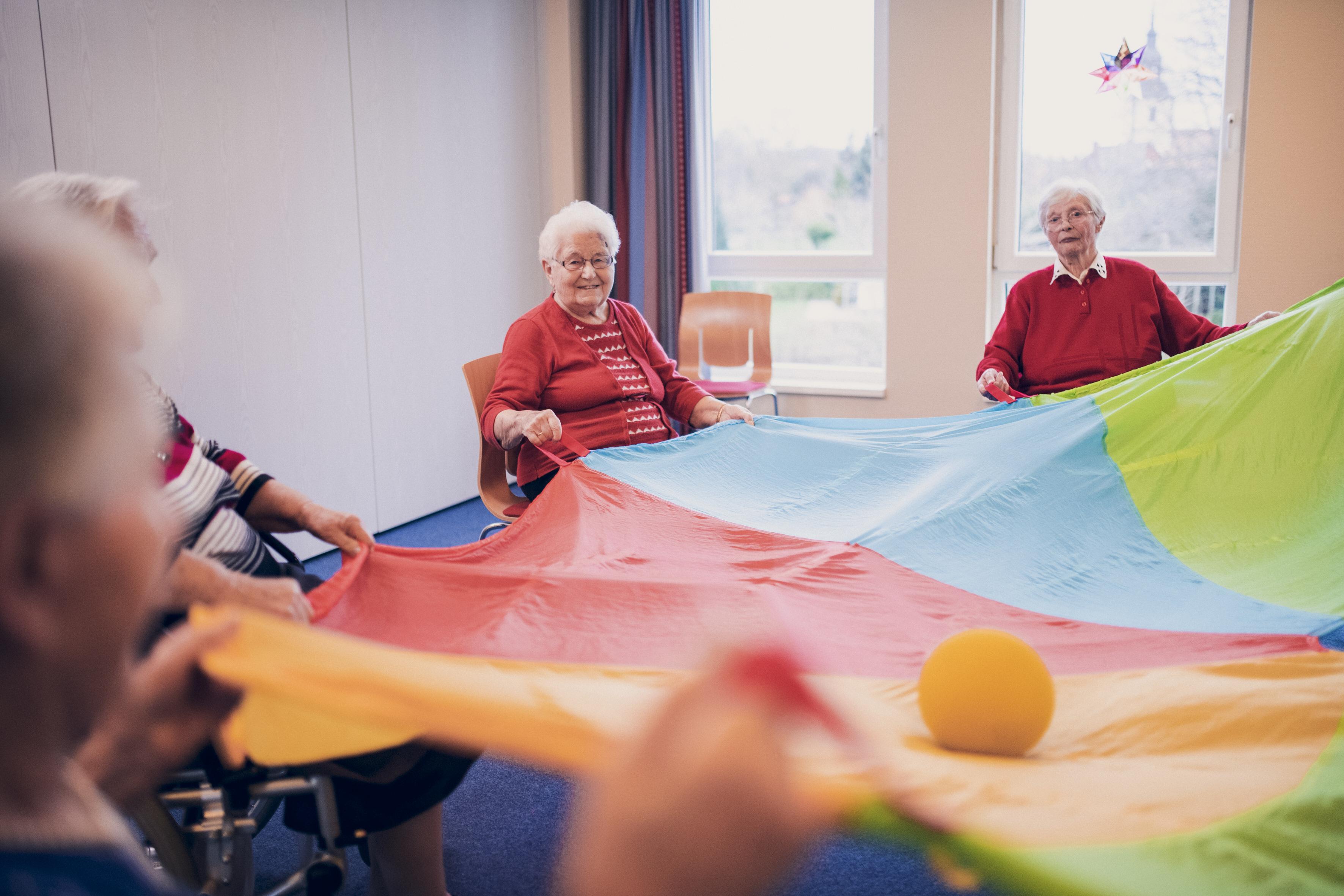 Seniorengruppe bei sportlichen Aktivitäten mit Ball und Tuch