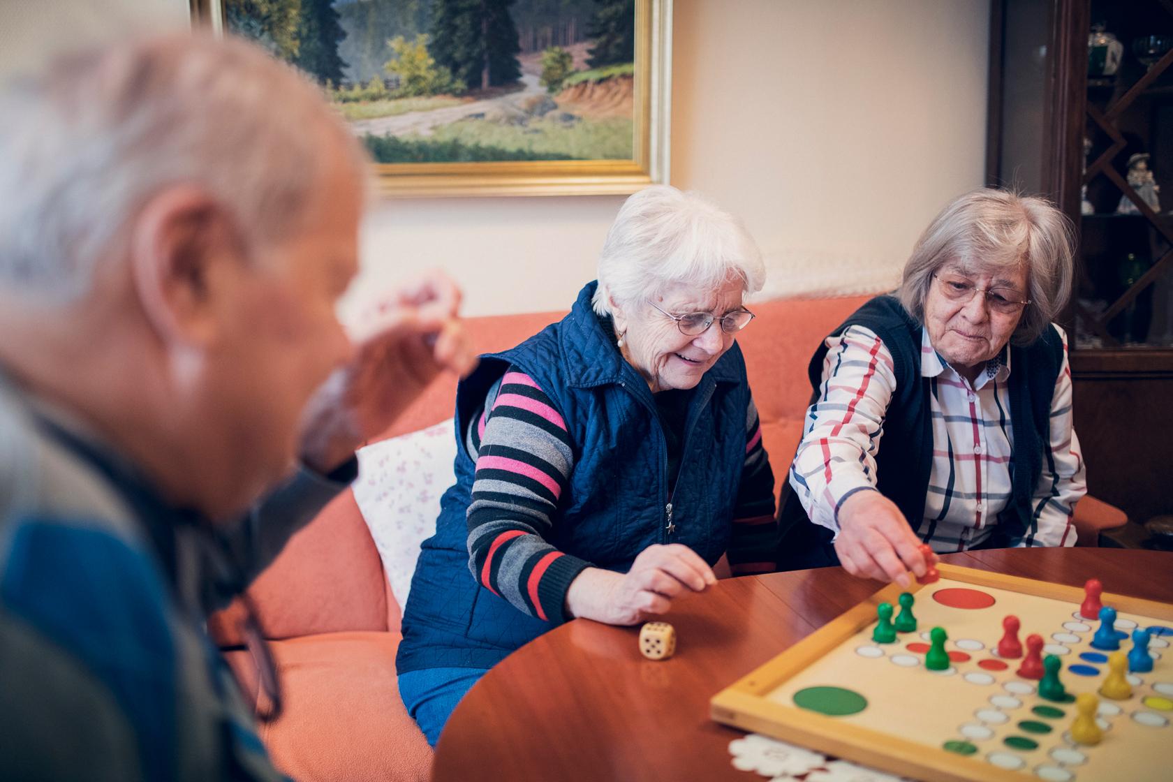 zwei Damen und ein Herr spielen Mensch-ärgere-dich-nicht
