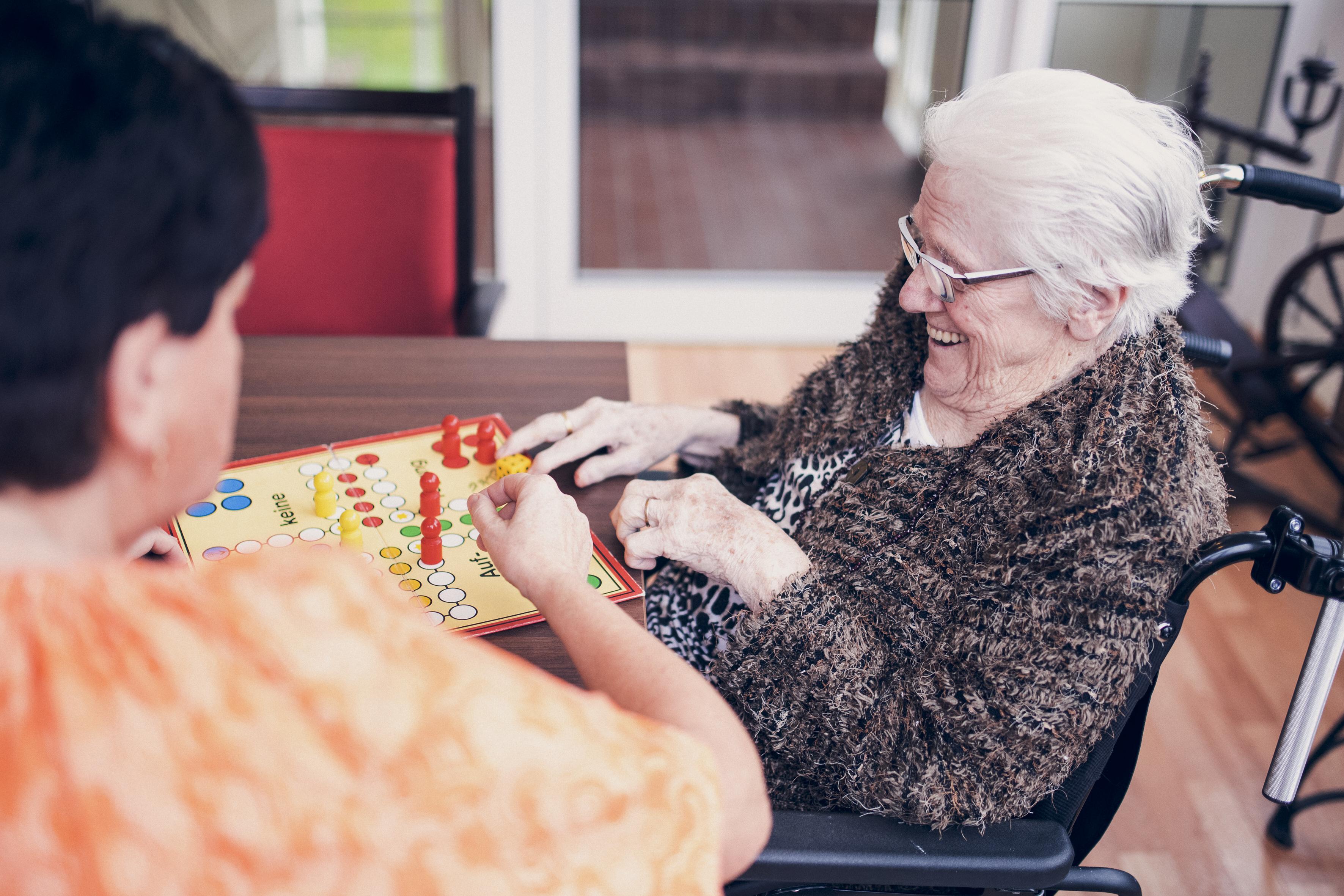 Eine Bewohnerin und eine Mitarbeiterin spielen zusammen ein Brettspiel