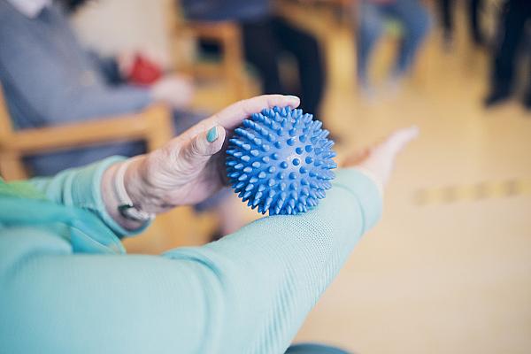 Eine Seniorin beschäftigt sich mit einem blauen Igelball