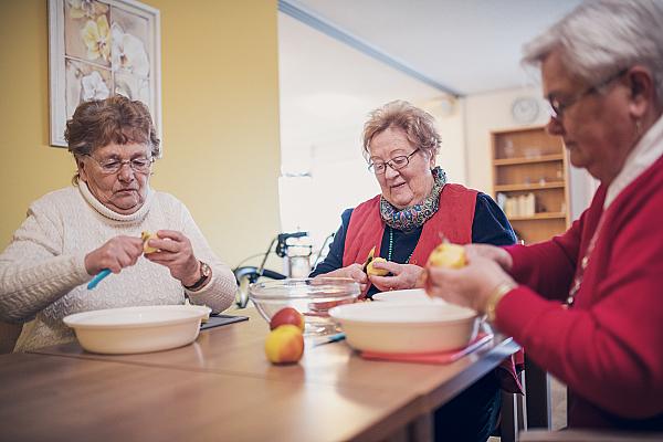 Drei Bewohnerinnen sitzen an einem Tisch und schälen Äpfel