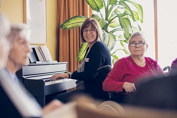 Bewohnerinnen lauschen einer Klavierspielerin
