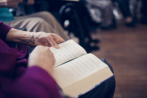 Ein Gesangbuch liegt aufgeschlagen auf dem Schoß einer Bewohnerin