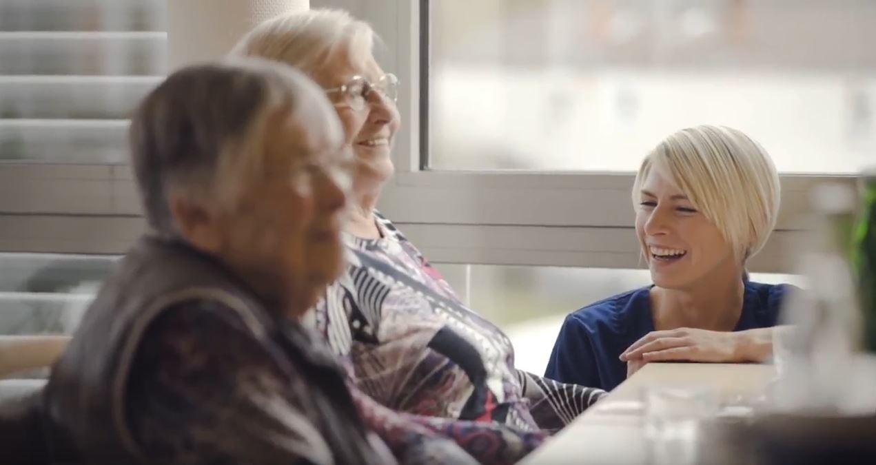 Pflegefachkraft lacht mit zwei Bewohnerinnen