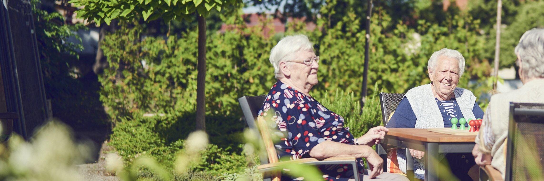 Bewohnende sitzen im Garten des Johanniterhauses Nebra