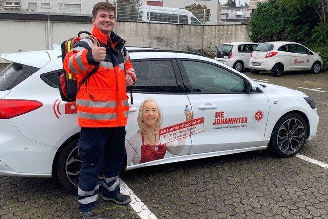 Matthias Pauls steht mit Notfallrucksack am Auto und hält den Daumen hoch
