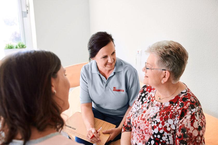 Eine Mitarbeiterin der Johanniter im Gespräch mit einer älteren Frau.