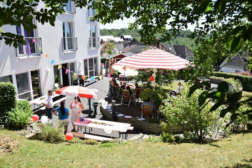 Viele Menschen stehen auf dem Platz vor Haus und feiern ein Sommerfest.