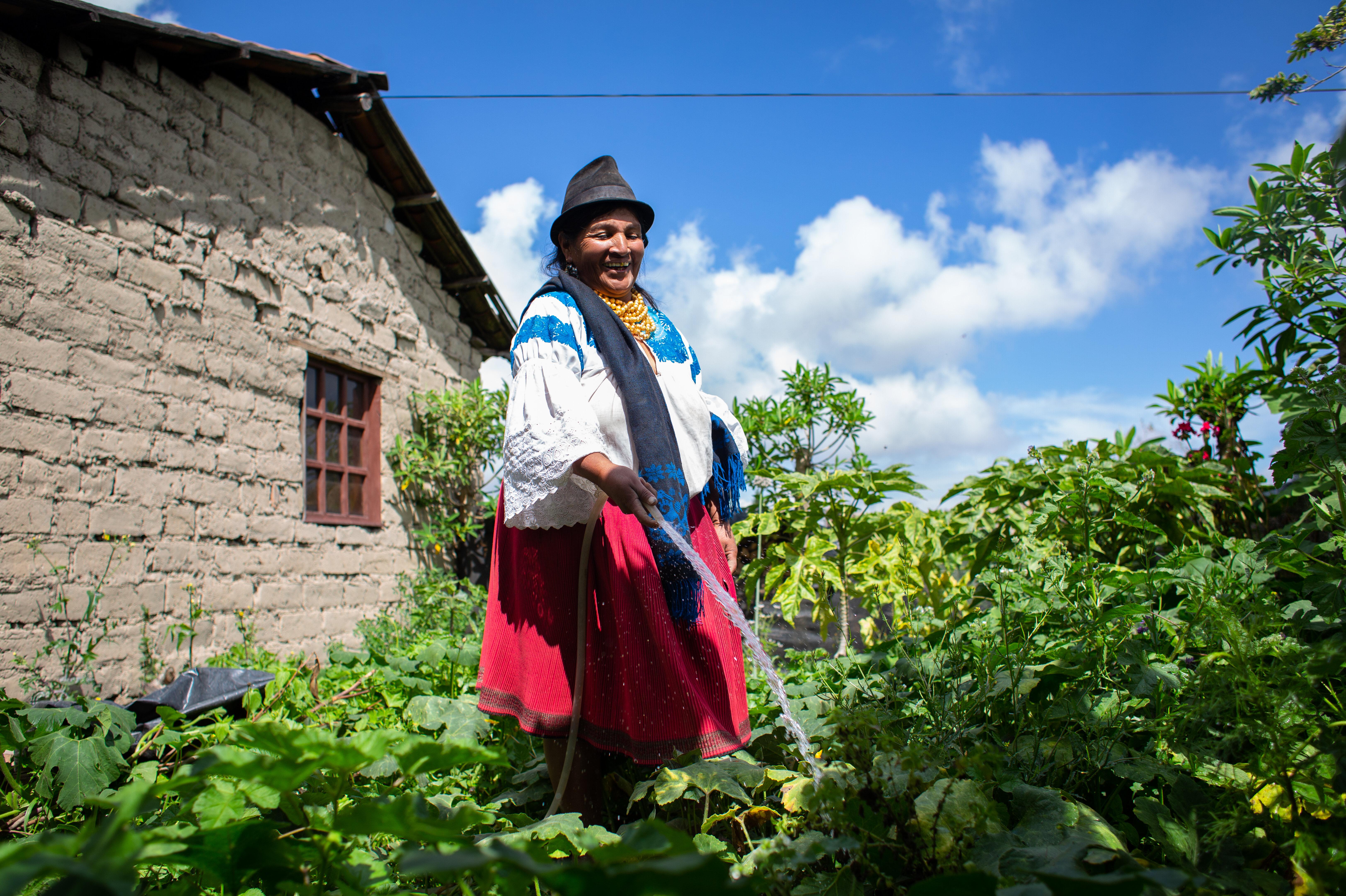 Eine Frau in traditioneller Kleidung gießt mit einem Wasserschlauch ihre Pflanzen.