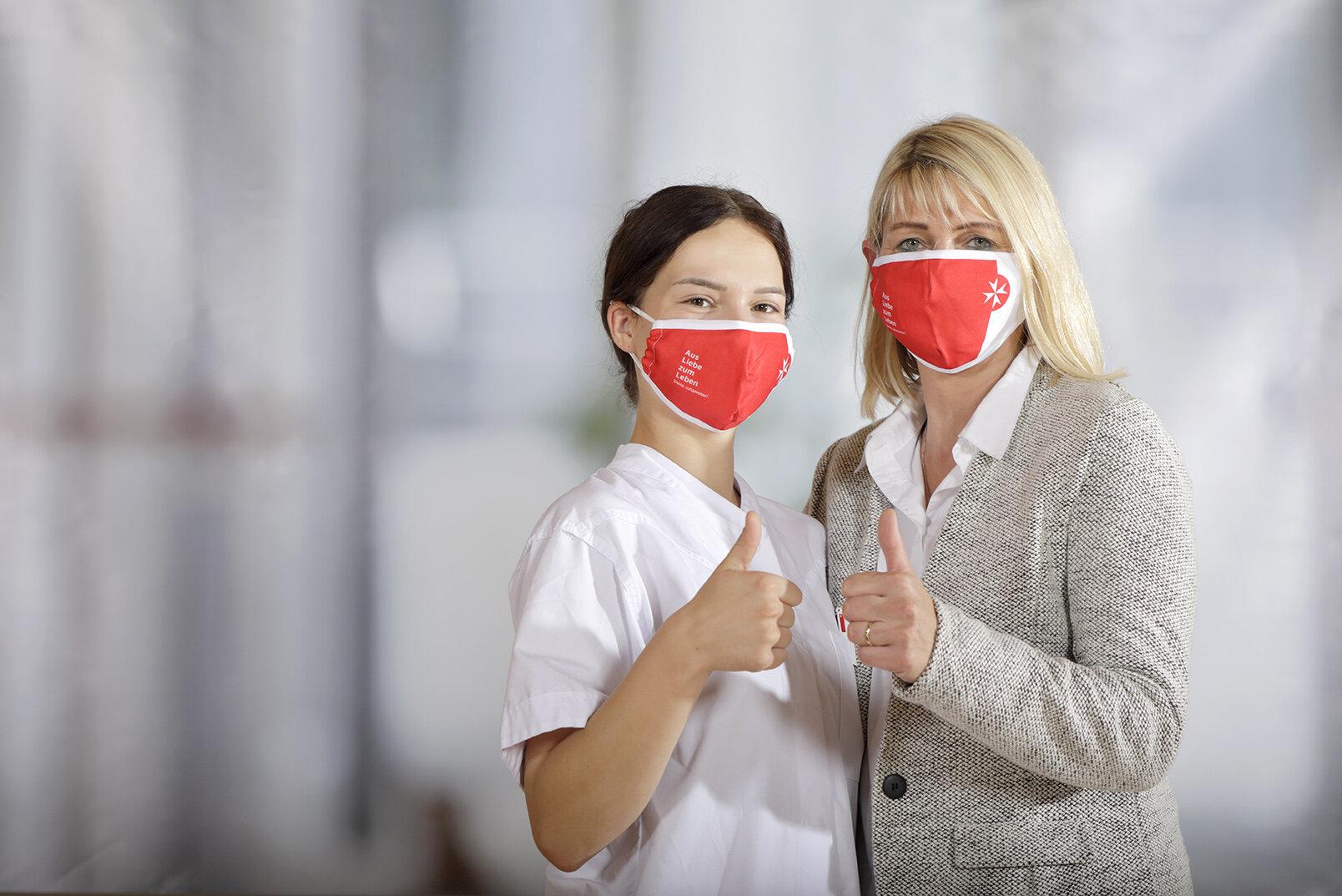 Zwei Pflegemitarbeiterinnen mit roten Johanniter-Masken