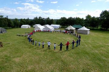 Junge Menschen stehen in einem Kreis und fassen sich an den Händen. Im Hintergrund stehen Zelte.