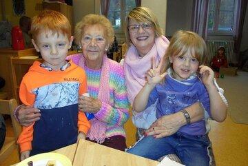 Zwei ältere Damen sitzen an einem kleinen Tisch und halten ihre Enkel im Arm.
