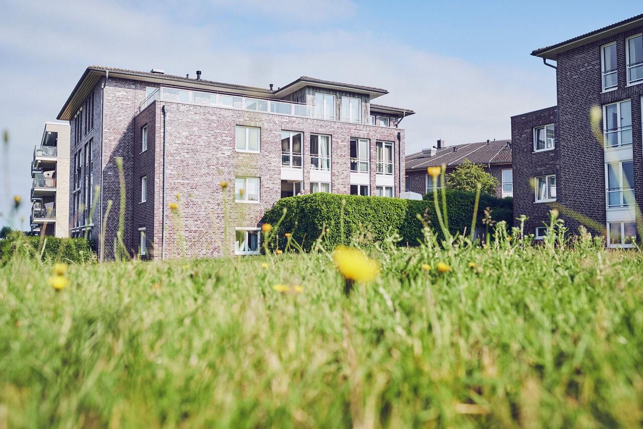 Blick auf mehrere gepflegte verklinkerte Häuser der Johanniter Seniorenanlage Heinrich-Gau in Wedel