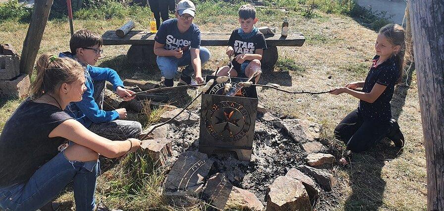 Kinder der Trauerbegleitungsgruppe Lacrima sitzen ums Feuer und machen Stockbrot.