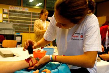 Ein Mädchen schminkt eine Wunde an einem Arm.