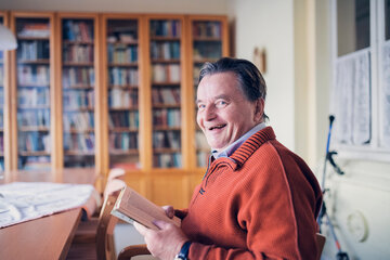 Ein Mann liest in der Bibliothek ein Buch