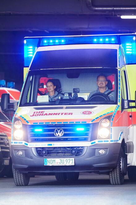 Ein Johanniter-Rettungswagen fährt mit Blaulicht aus der Fahrzeughalle.