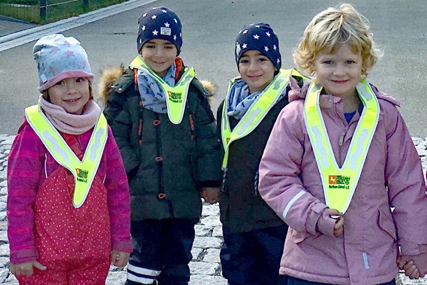 Vier Kinder der Kita am Wieter präsentieren die neuen gelben Warndreiecke.
