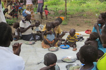 Women sitting on the floor feeding their children with the food they cooked together