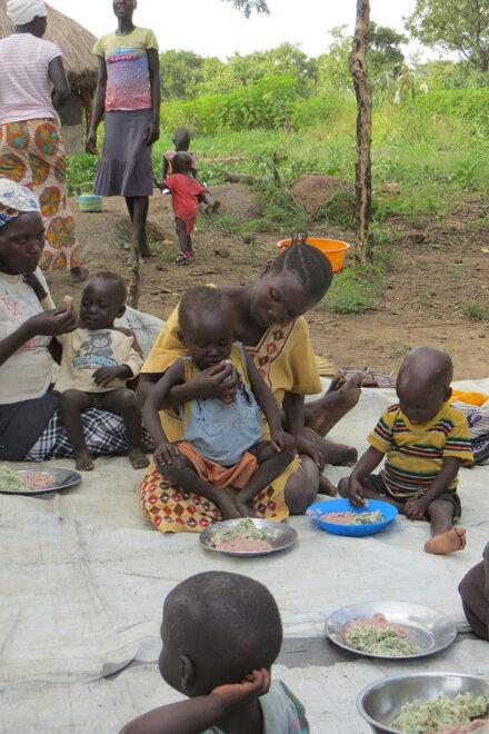 Auf dem Boden sitzende Frauen füttern ihre Kinder mit dem gemeinsam gekochten Essen