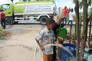 A little boy fills a barrel with drinking water from an INANTA tanker