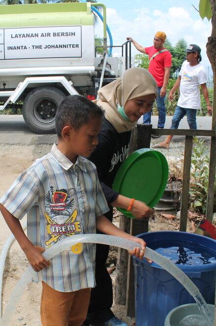 Ein kleiner Junge füllt ein Fass mit Trinkwagen aus einem Tanklaster von INANTA