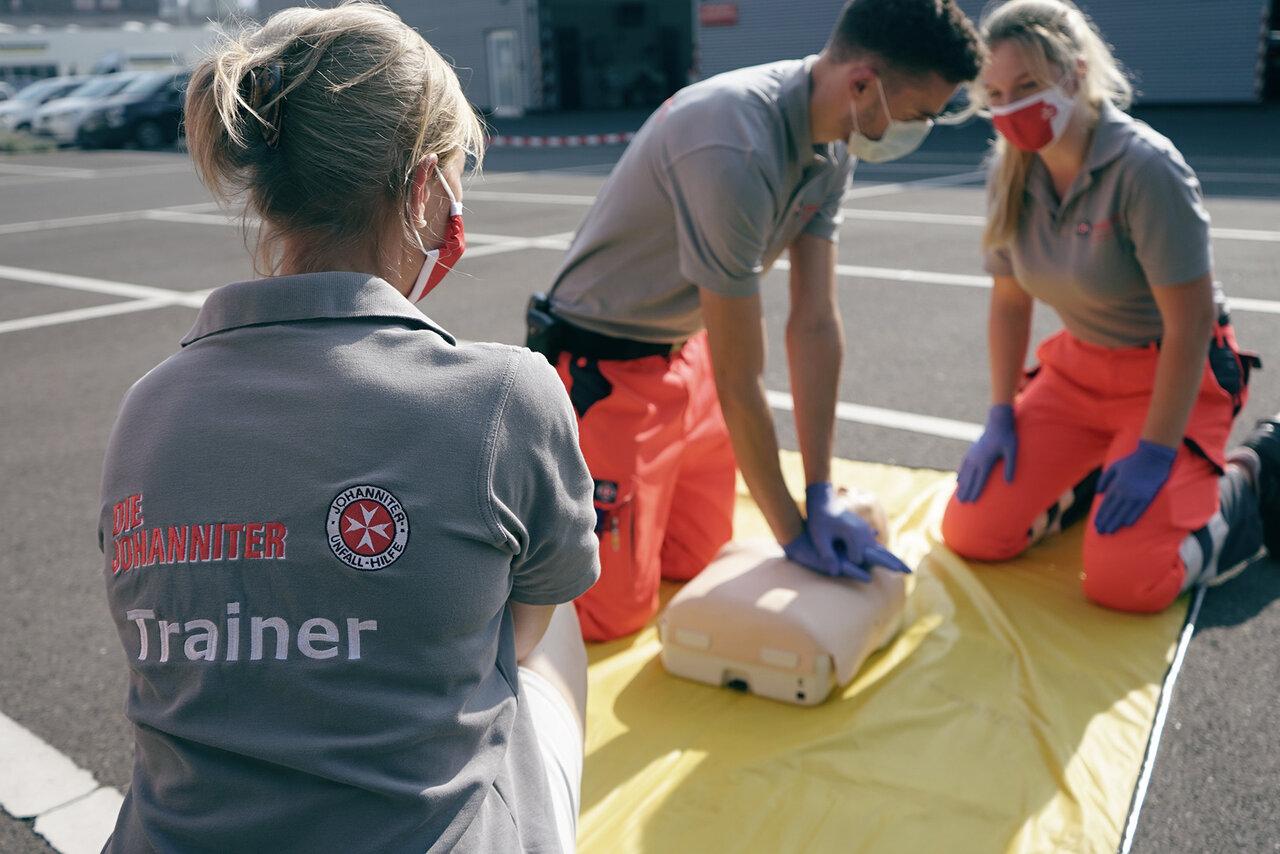 Eine Johanniter-Trainerin in grauem Poloshirt beobachtet zwei Personen, die an einer Puppe Wiederbelebung trainieren