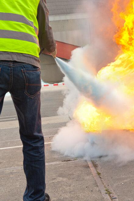 Eine Person löscht mit einem Feuerlöscher ein Feuer