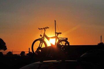 Ein Fahrrad steht auf einem Autodach vor dem Sonnenuntergang