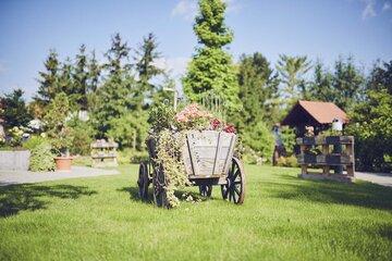 Ein altes Fuhrwerk dient als Blumenbeet