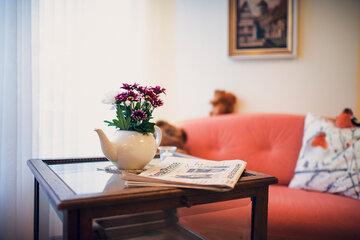 Eine kleine rote Blume auf einem Glastisch im Johanneshaus Empelde