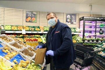 Johanniter-Mitarbeiter packt am Stand im Supermarkt Obst ein.