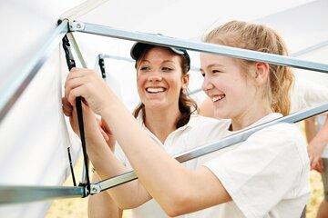 Zwei Mädchen befestigen die Zeltstange eines Gerüstzeltes.