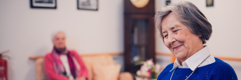 Eine Bewohnerin in blauem Pullover liest im Johanniter-Stift